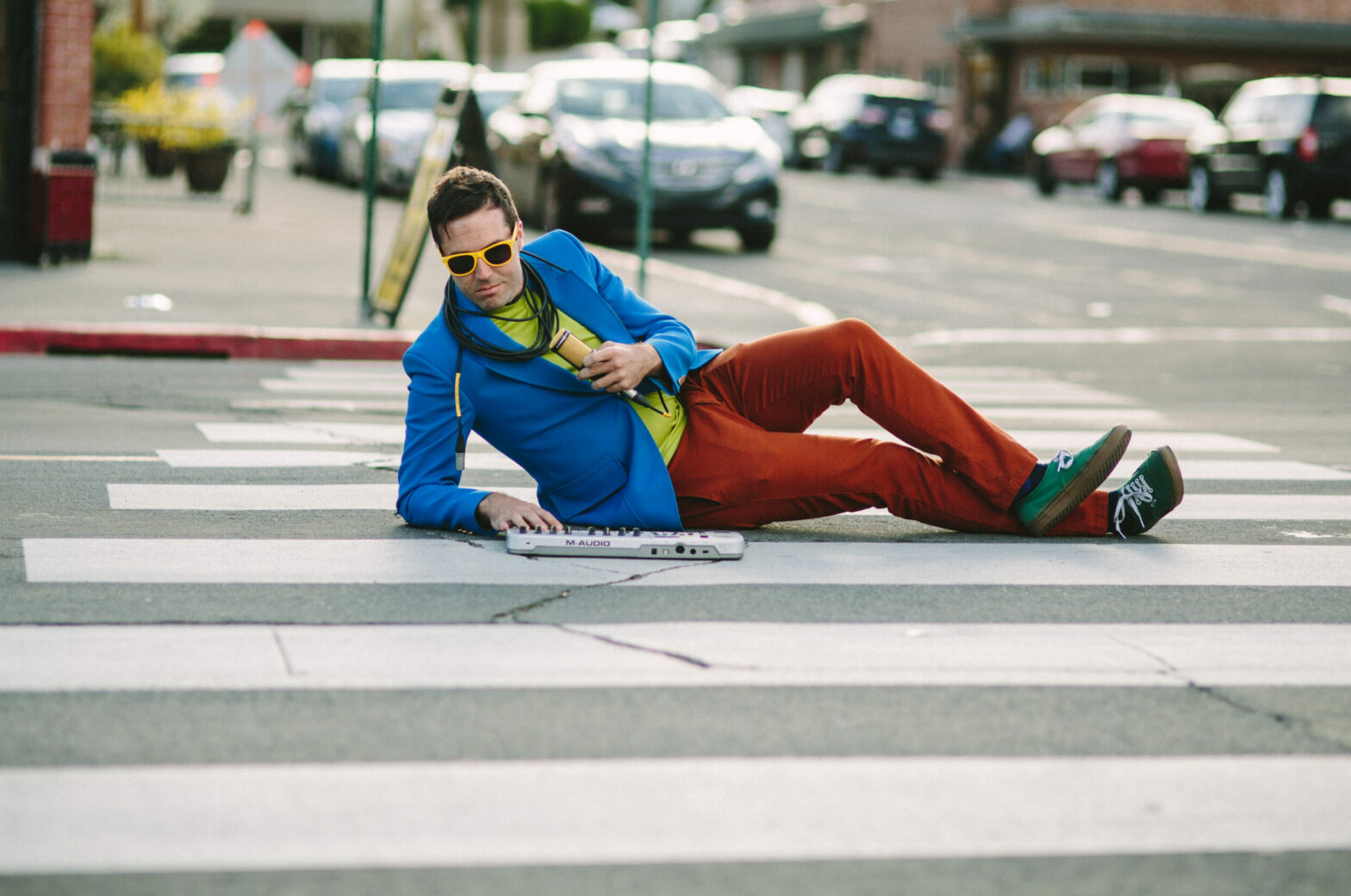 Ford Corl holds a microphone and plays a small keyboard while laying in a crosswalk.