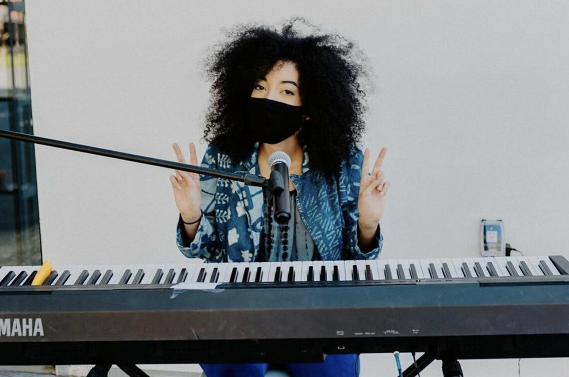 Grace Hayes, wearing a face mask, makes peace signs with her hands in front of a keyboard and microphone.