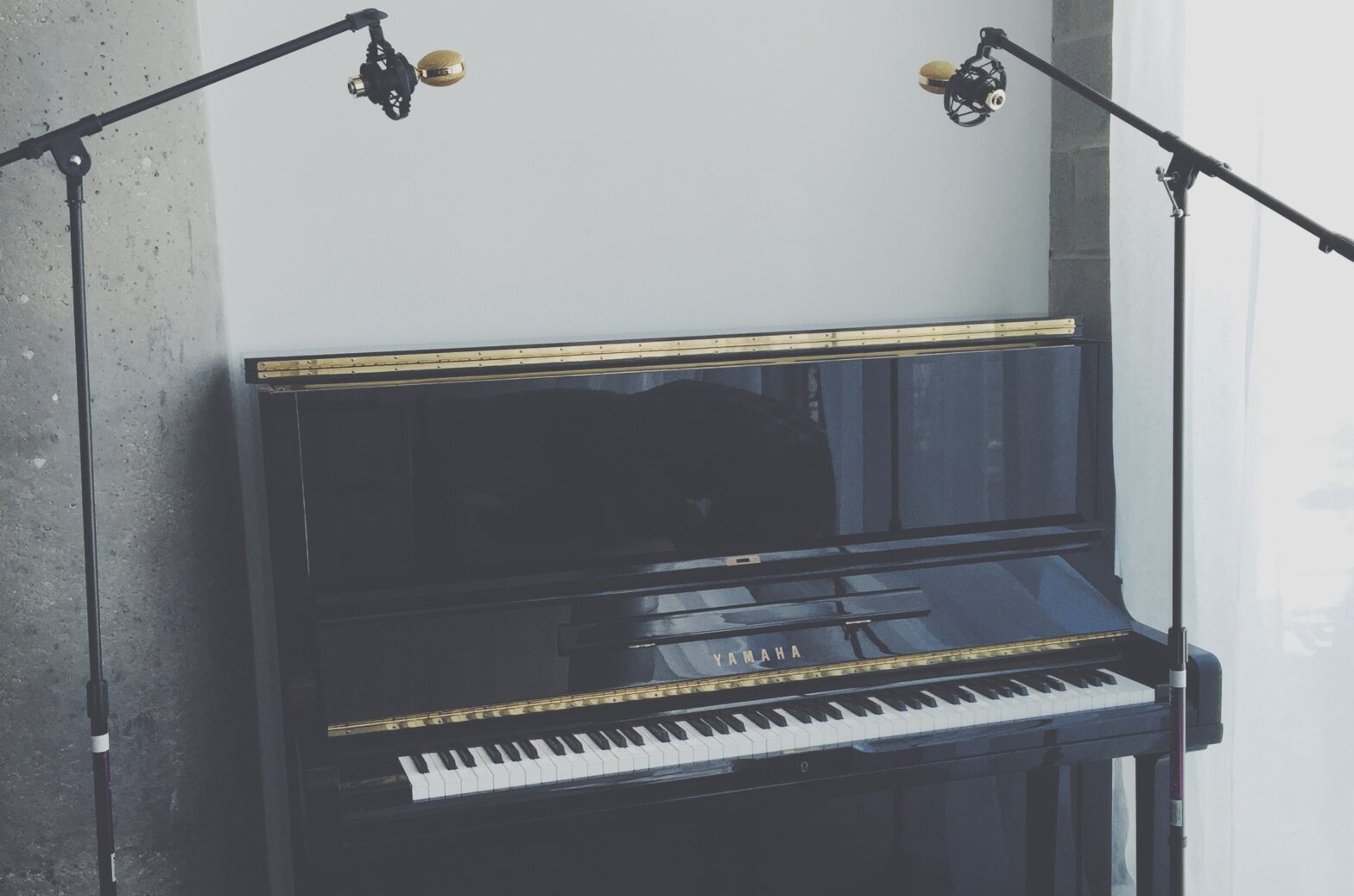 A black upright piano with two microphones sits in a gray room.