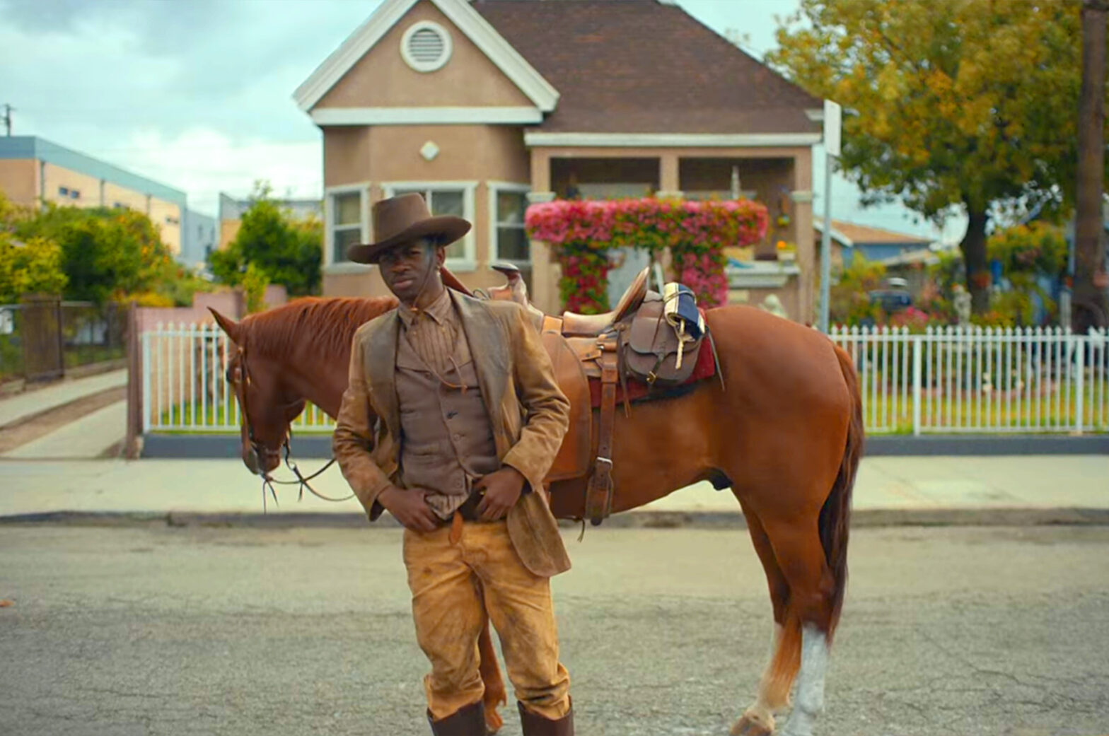 """Still from the music video for Lil Nas X's """"Old Town Road."""" Lil Nas X, in country western clothing in front of a horse, stands in an Los Angeles neighbordhood."""