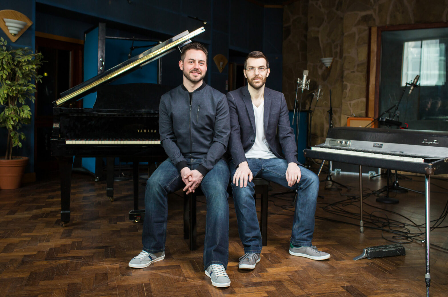 Simon Barber and Brian O'Connor, hosts of the Sodajerker podcast, sit on a piano bench in a room with a grand piano and keyboard.