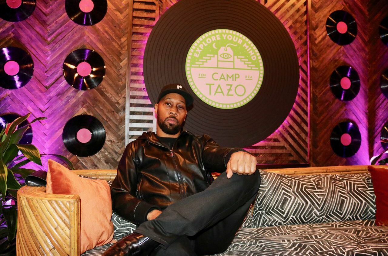 """Rza sits on a leopard-print couch in front of a wall of vinyl records and a large, promotional record-shaped poster that reads """"Camp Tazo"""""""