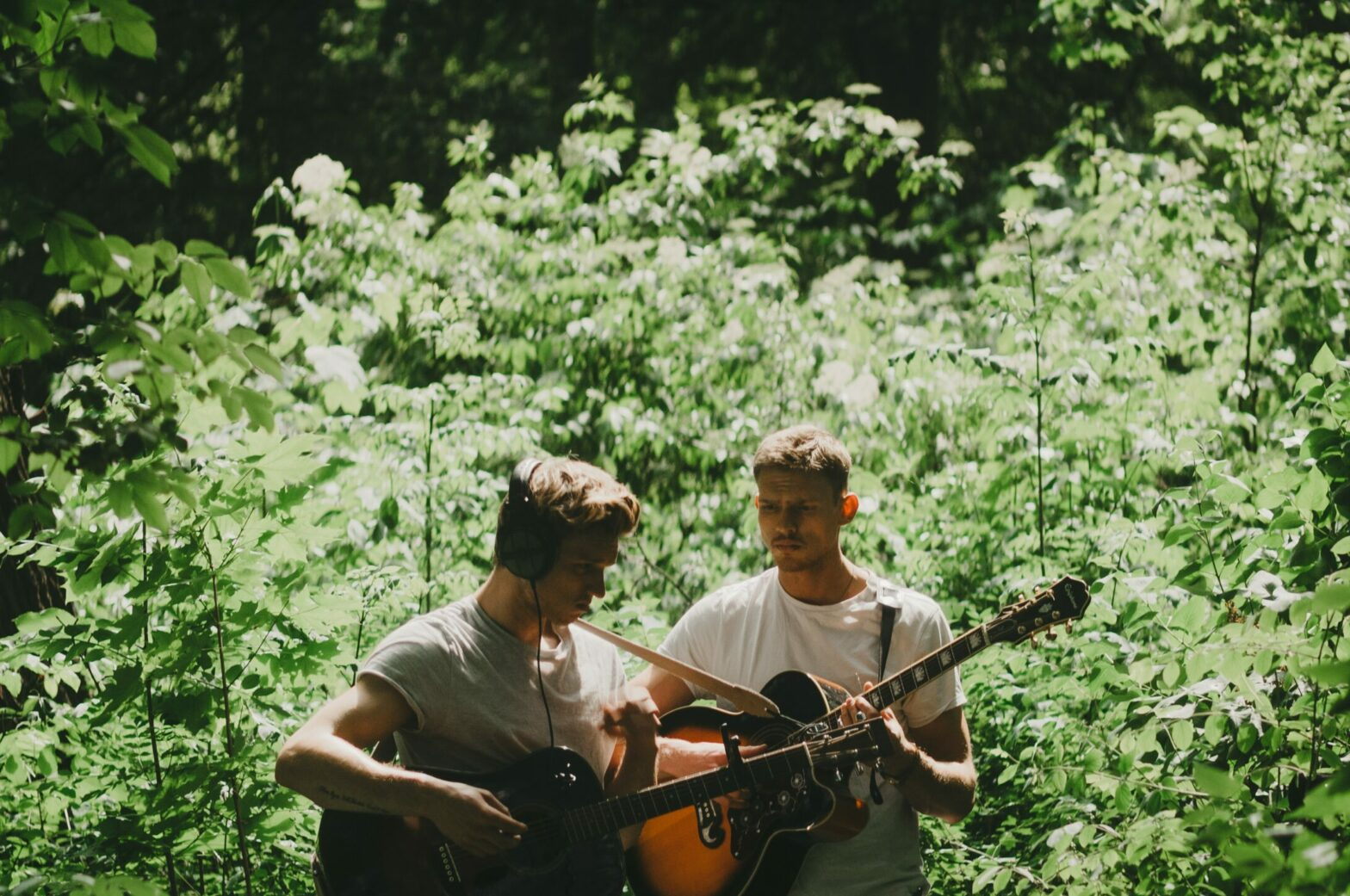 Two people stand with acoustic guitars in front of leafy green bushes.