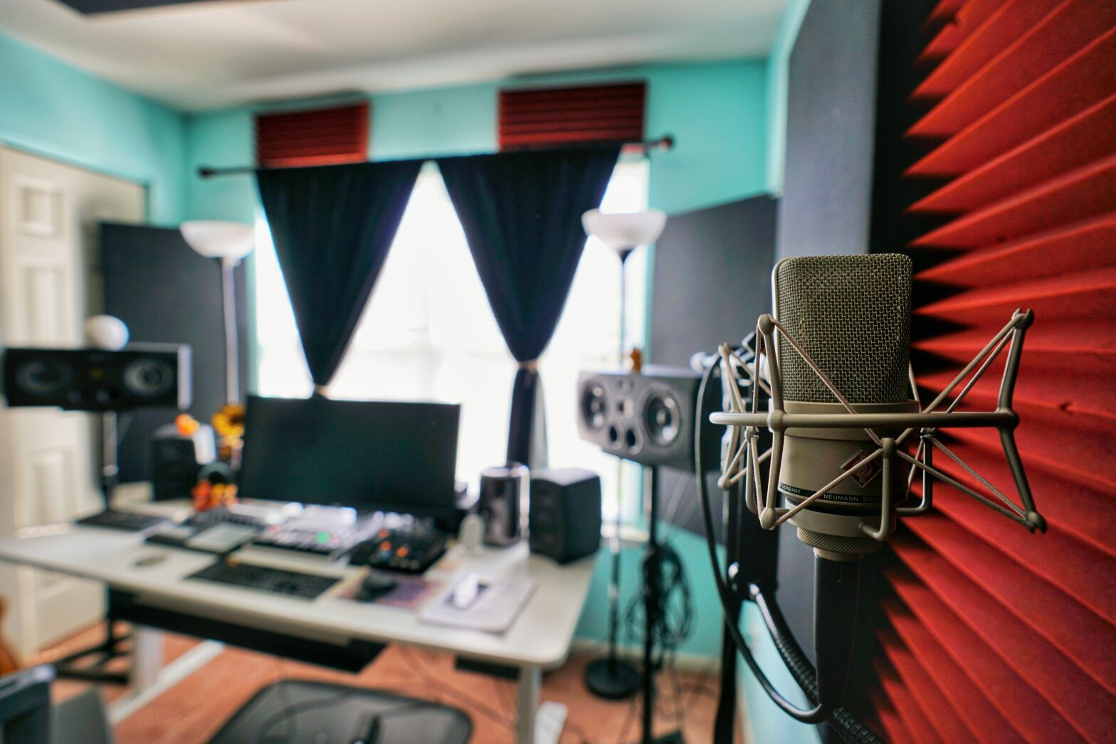 A home music recording studio is pictured, with microphones, a desktop computer, speakers, and soundproofing on the walls.