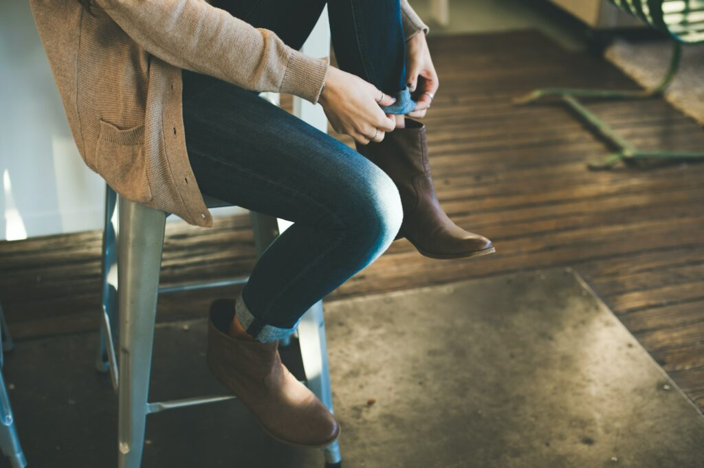 A person sits on a barstool, with only their legs in frame, as they cuff their jeans into their cowboy-style boots.