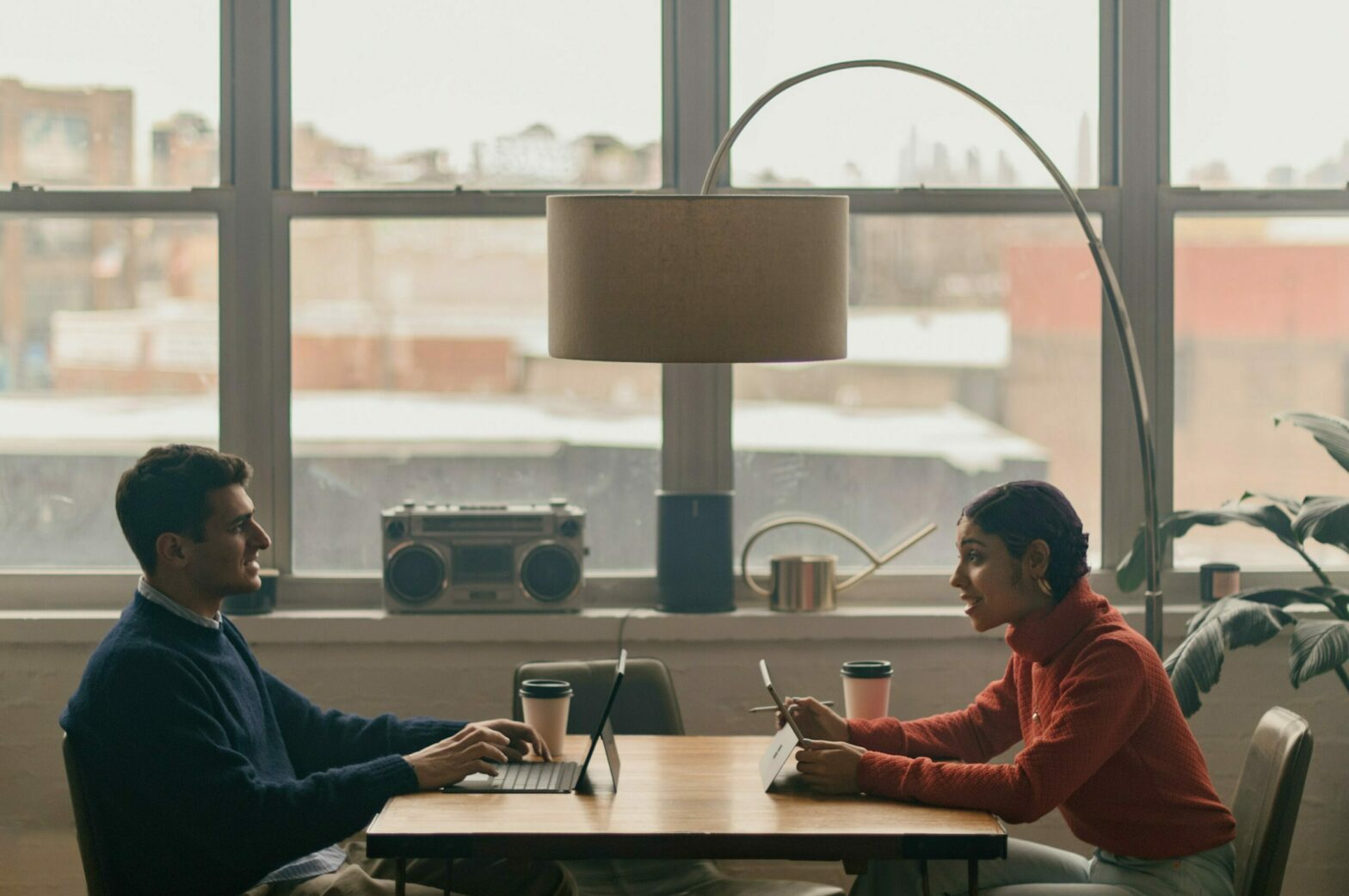 Two people sit and converse, facing each other, at a table in front of a wall of large windows.